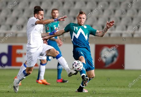Stock Photo of Cyprus' Chambos Kyriakou, left, and Slovenia's Jasmin Kurtic challenge for the ball during the World Cup 2022 group H qualifying soccer match between Cyprus and Slovenia at GSP stadium in Nicosia, Cyprus