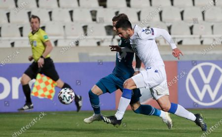 Slovenia's Luka Zahovic, left, and Cyprus' Konstantinos Laifis challenge for the ball during the World Cup 2022 group H qualifying soccer match between Cyprus and Slovenia at GSP stadium in Nicosia, Cyprus