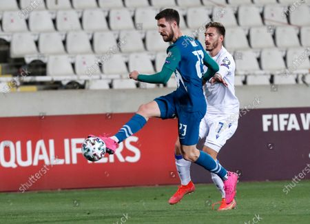 Slovenia's Kenan Bajric, left, and Cyprus' Minas Antoniou challenge for the ball during the World Cup 2022 group H qualifying soccer match between Cyprus and Slovenia at GSP stadium in Nicosia, Cyprus
