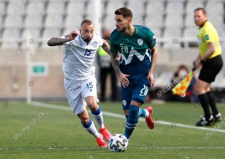 Cyprus' Fotis Papoulis, left, and Slovenia's Petar Stojanovic challenge for the ball during the World Cup 2022 group H qualifying soccer match between Cyprus and Slovenia at GSP stadium in Nicosia, Cyprus