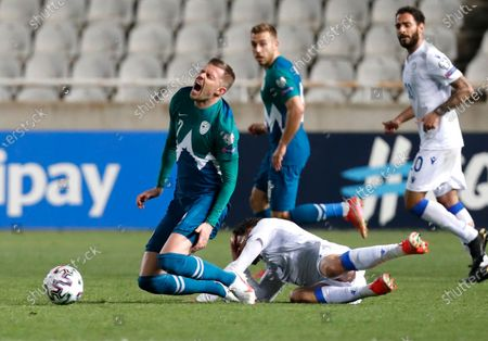 Slovenia's Josip Ilicic, left, and Cyprus' Nicholas Ioannou challenge for the ball during the World Cup 2022 group H qualifying soccer match between Cyprus and Slovenia at GSP stadium in Nicosia, Cyprus