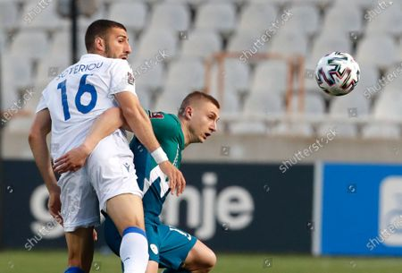 Cyprus' Costas Soteriou, left, and Slovenia's Blaz Kramer challenge for the ball during the World Cup 2022 group H qualifying soccer match between Cyprus and Slovenia at GSP stadium in Nicosia, Cyprus