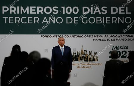 Mexican President Andres Manuel Lopez Obrador stands at attention during a ceremony before a news conference marking the 100th day of his third year in office, at the National Palace in Mexico City