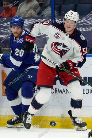 Columbus Blue Jackets left wing Eric Robinson (50) takes the puck away from Tampa Bay Lightning center Blake Coleman (20) during the first period of an NHL hockey game, in Tampa, Fla