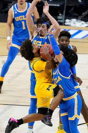 Michigan guard Mike Smith, left, is fouled by UCLA guard Tyger Campbell, right, during the first half of an Elite 8 game in the NCAA men's college basketball tournament at Lucas Oil Stadium, in Indianapolis