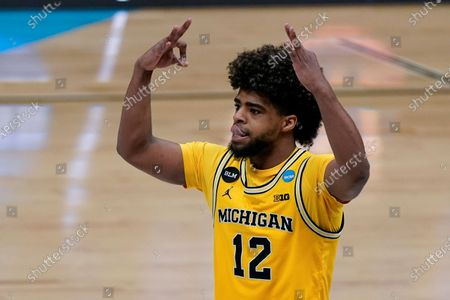 Stock Image of Michigan guard Mike Smith celebrates after making a 3-point basket during the second half of an Elite 8 game against UCLA in the NCAA men's college basketball tournament at Lucas Oil Stadium, in Indianapolis