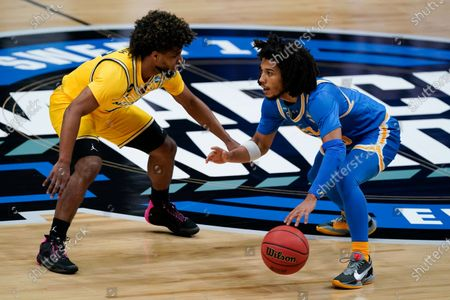 Guard Tyger Campbell, right, drives past Michigan guard Mike Smith, left, during the first half of an Elite 8 game in the NCAA men's college basketball tournament at Lucas Oil Stadium, in Indianapolis