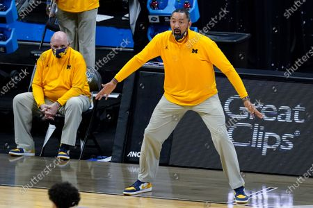 Michigan head coach Juwan Howard reacts to a play as assistant coach Phil Martelli looks on from the bench during the first half of an Elite 8 game against UCLA in the NCAA men's college basketball tournament at Lucas Oil Stadium, in Indianapolis