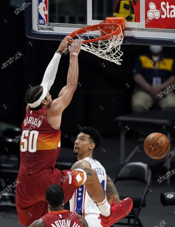 Denver Nuggets forward Aaron Gordon (50) hangs from the rim after dunking the ball for a basket as Philadelphia 76ers forward Danny Green looks on in the second half of an NBA basketball game, in Denver