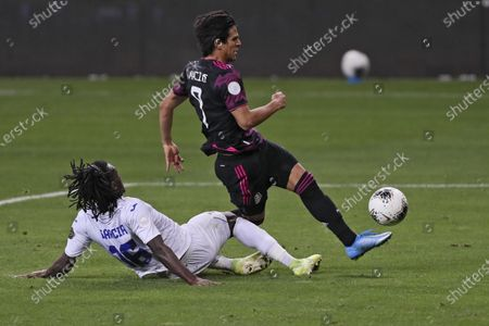 Mexico's Jose Macias, center, is tackled by Honduras' Jose Garcia during the Concacaf Men's Olympic qualifying championship final soccer match in Guadalajara, Mexico