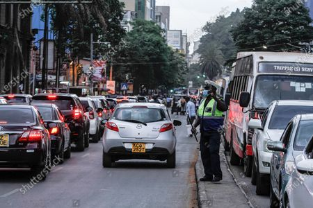 A Nairobi County traffic Marshall controls traffic along Moi avenue as motorist rush home to beat 8pm - 4am curfew.On Friday, March 26th, President Uhuru Kenyatta announced a  partial lockdown and instituted new curfew measures to start from 8pm to 4am. The new measures to curb the spread of COVID-19 include placing Nairobi, Nakuru, Kiambu and Machakos counties under partial lockdown as well as closing restaurants, bars and schools nationwide amid a third wave of COVID-19 across the country.