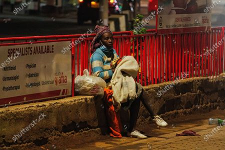 A homeless Kenyan lady holding her baby as she ponders her next move as the new 8pm-4am curfew takes effects.On Friday, March 26th, President Uhuru Kenyatta announced a  partial lockdown and instituted new curfew measures to start from 8pm to 4am. The new measures to curb the spread of COVID-19 include placing Nairobi, Nakuru, Kiambu and Machakos counties under partial lockdown as well as closing restaurants, bars and schools nationwide amid a third wave of COVID-19 across the country.