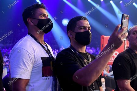 Latrell Mitchell and Cody Walker watch on as Paul Fleming enters for his undercard bout during the Steel City Showdown ahead of the super welterweight bout between Australia's Tim Tszyu and Ireland's Dennis Hogan at the Newcastle Entertainment Centre, Newcastle, Australia, 31 March 2021.