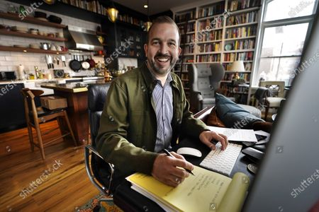 Matt Roberts, a writer on the SAG Awards, works at his desk in his apartment, in Portland, Maine. The Screen Actors Guild Awards airs Sunday at 9 p.m. EDT on TNT and TBS