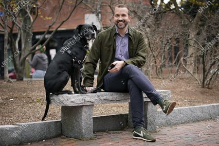 Matt Roberts, a writer on the SAG Awards, sits with his dog, Augie, at a downtown park, in Portland, Maine