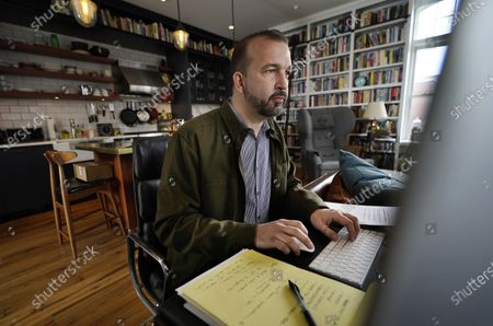 Stock Picture of Matt Roberts, a writer on the SAG Awards, works at his desk in his apartment, in Portland, Maine