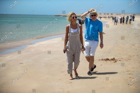 Karen and David Richards collect litter on the beach during the 2021 Extreme E Desert X Prix