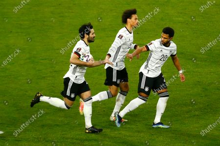 Germany's Ilkay Gundogan, left, celebrates with his teammates Leroy Sane and Serge Gnabry after scoring on a penalty his side's first goal during the World Cup 2022 group J qualifying soccer match between Germany and North Macedonia in Duisburg, Germany