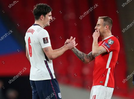 England's Harry Maguire, left, greets Poland's Kamil Grosicki after the World Cup 2022 group I qualifying soccer match between England and Poland at Wembley stadium in London, England, . England won the match 2-1