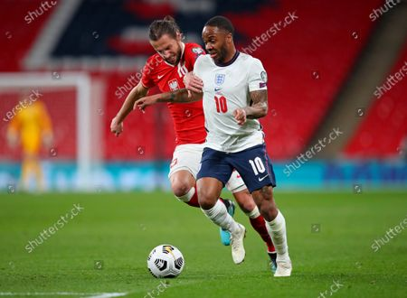 Poland's Grzegorz Krychowiak, left, challenges England's Raheem Sterling during the World Cup 2022 group I qualifying soccer match between England and Poland at Wembley stadium in London, England