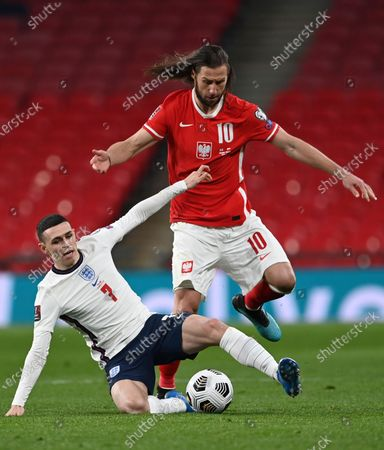 England's Phil Foden, left, challenges for the ball with Poland's Grzegorz Krychowiak during the World Cup 2022 Group I qualifying soccer match between England and Poland at Wembley Stadium in London, England