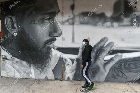 People walk past a mural of American rapper Nipsey Hussle in the Bushwick neighborhood of Brooklyn.