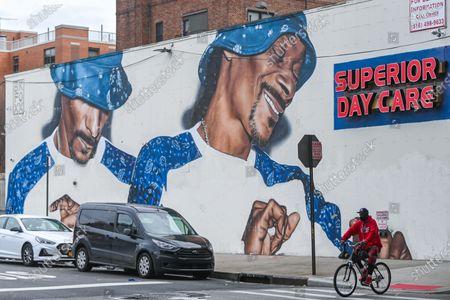 People walk past a mural of American rapper Snoop Dogg in the Ocean Hill Brownsville neighborhood of Brooklyn.