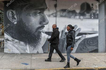 Stock Image of People walk past a mural of American rapper Nipsey Hussle in the Bushwick neighborhood of Brooklyn.