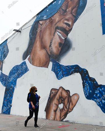 Stock Image of People walk past a mural of American rapper Snoop Dogg in the Ocean Hill Brownsville neighborhood of Brooklyn.