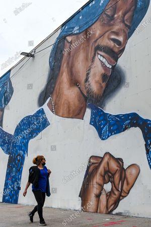 Stock Photo of People walk past a mural of American rapper Snoop Dogg in the Ocean Hill Brownsville neighborhood of Brooklyn.