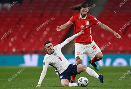 England's Phil Foden (L) and Grzegorz Krychowiak of Poland (R) during the FIFA World Cup 2022 qualifying soccer match between England and Poland in London, Britain, 31 March 2021.