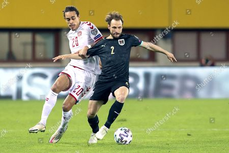 Denmark's Yussuf Poulsen, left, fights for the ball with Austria's Andreas Ulmer during the World Cup 2022 group F qualifying soccer match between Austria and Denmark at Ernst-Happel-Stadium in Vienna, Austria
