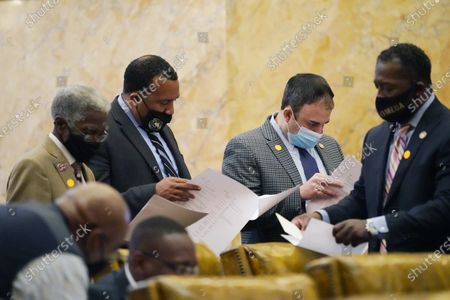 Stock Image of Democratic Representatives Rufus Straughter of Belzoni, left, Jeffery Harness of Fayette, second from left, Tom Miles of Forest, second from right and Christopher Bell of Jackson, right, review a breakdown of bond bill allocations by counties, at the Capitol in Jackson, Miss. Lawmakers in both chambers worked steadily to meet deadlines on the remaining legislation to be completed this session