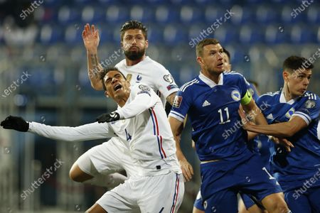 Bosnian player Edin Dzeko challenge for ball with France Raphael Varane