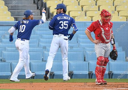LOS ANGELES CALIFORNIA MARCH 30, 2021-Dodgers Cody Bellinger celebrates his two-run home run with Just Turner as Angels catcher Max Stassi looks on in the 1st inning during the Freeway Series at Dodger Stadium Tuesday. (Wally Skalij/Los Angeles Times)