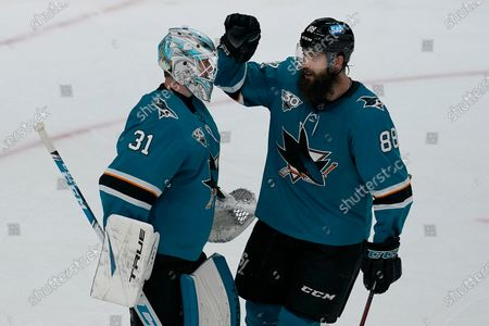 San Jose Sharks goaltender Martin Jones (31) celebrates with defenseman Brent Burns (88) after the Sharks defeated the Minnesota Wild in an NHL hockey game in San Jose, Calif