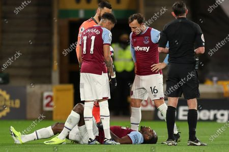 Michail Antonio of West Ham United lies on the ground as he is assisted by Jesse Lingard and Mark Noble of West Ham United, Rui Patrício of Wolverhampton Wanderers and Referee Michael Oliver