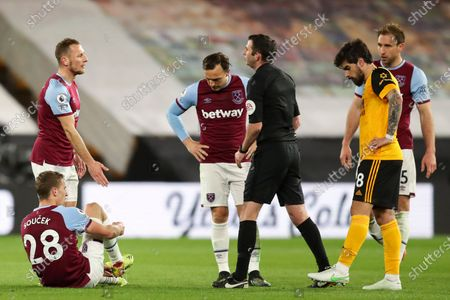 Vladimir Coufal of West Ham United speaks with Referee Michael Oliver as Tomas Soucek of West Ham United takes of his football boot revealing his sock to be covered in blood after being stepped on