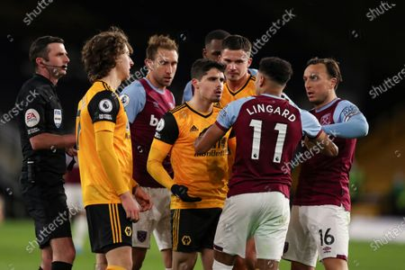 Pedro Neto of Wolverhampton Wanderers and Jesse Lingard of West Ham United clash at the full-time whistle as their teammates and Referee Michael Oliver gather around closely