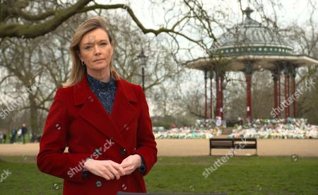 Julie Etchingham stands in front of the band stand on Clapham Common where 100 of people have left floral tributes in memory of Sarah Everard