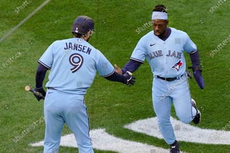 Toronto Blue Jays on-deck batter Danny Jansen (9) congratulates Jonathan Davis after Davis scored on Randal Grichuk's tenth inning double in a major league baseball game New York Yankees on opening day at Yankee Stadium, in New York. The Blue Jays defeated the Yankees 3-2