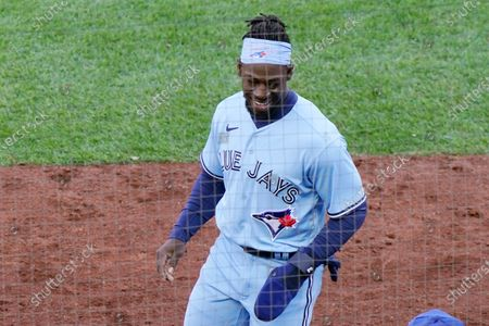 Toronto Blue Jays Jonathan Davis smiles as he enters the dugout after scoring on Randal Grichuk's tenth inning RBI double in a major league baseball game against the New York Yankees on opening day at Yankee Stadium, in New York. The Blue Jays defeated the Yankees 3-2