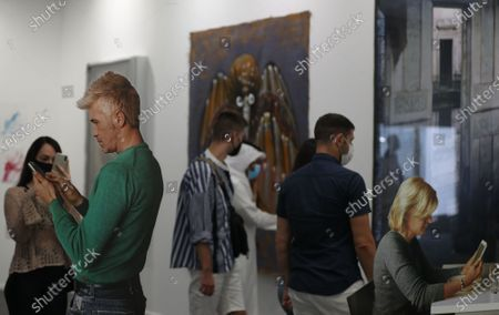 Visitors look at the artwork 'Smartphone Ð seated woman and standing man, 2018 ' by American artist Michelangelo Pistoletto during the 14th annual Art Dubai exhibition at Dubai International Financial Centre (DIFC) in the Gulf emirate of Dubai, United Arab Emirates, 01 April 2021.