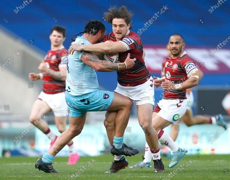 Wigan Warriors' Liam Byrne and Wakefield Trinity's David Fifita in action