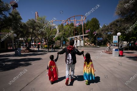 Stock Photo of Christian Castro, center, and his two children, Damian, left, and Destiny visit Six Flags Magic Mountain on its first day of reopening to members and pass holders in Valencia, Calif., . The theme park had been closed since March 2020 due to the coronavirus pandemic