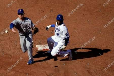 Texas Rangers second baseman Nick Solak throws to first too late for the double play on a ball hit by Kansas City Royals' Salvador Perez, after forcing Carlos Santana (41) out at second during the second inning of a baseball game, in Kansas City, Mo