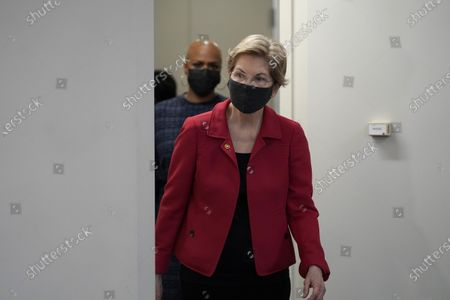 Sen. Elizabeth Warren, D-Mass., front, and U.S. Rep. Ayanna Pressley, D-Mass., behind, arrive before the start of a news conference, in Boston. The news conference was held to call on President Biden to use the Higher Education Act to cancel a share of student loan debt for students with federal loans
