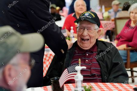 Howard Bennett, a U.S. Army Air Corps veteran, laughs as he speaks with his son, Steve Bennett, left, visiting for the first time without the use of protective garments at the Mississippi State Veterans Home in Collins, Miss., . Due to the relaxation of protocols designed to slow the spread of coronavirus, the veterans home allowed indoor, in-person visits between veterans and two family members without the use of PPE for the first time since March of 2020. Previously all visits had been socially-distanced through the facility's windows, or outdoors with a limited number of covid tested family members wearing gowns, face masks and gloves