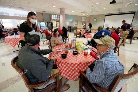 """Stock Picture of John Pipkins, a Vietnam era veteran of the U.S. Marine Corps, right, enjoys a lunch with his """"adoptive"""" family of Jason Davis, left, and his wife Cathy Davis of Moselle, for the first time without the use of protective garments at the Mississippi State Veterans Home in Collins, Miss., . Due to the relaxation of protocols designed to slow the spread of coronavirus, the veterans home allowed indoor, in-person visits between veterans and two family members without the use of PPE for the first time since March of 2020"""