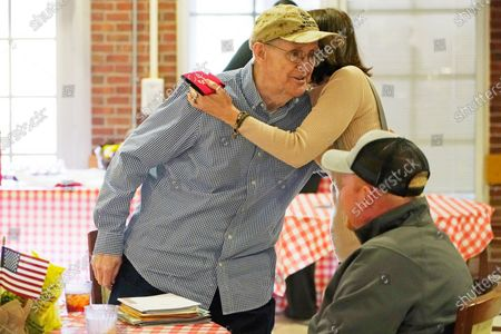 """John Pipkins, a Vietnam era veteran of the U.S. Marine Corps, left, hugs Cathy Davis, who, with her husband Jason Davis, seated, have """"adopted"""" the veteran and are now his """"family,"""" at the Mississippi State Veterans Home in Collins, Miss., . The friends are now meeting for the first time without the use of protective garments. Due to the relaxation of protocols designed to slow the spread of coronavirus, the veterans home allowed indoor, in-person visits between veterans and two family members without the use of PPE for the first time since March of 2020"""